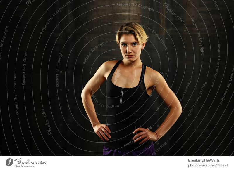 Close up front upper body portrait of one young athletic woman in sportswear in gym over dark background, looking at camera Lifestyle Sports Fitness