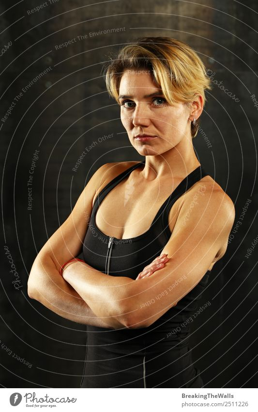 Close up front upper body portrait of one young athletic woman in sportswear in gym over dark background, looking at camera Sports Fitness Sports Training