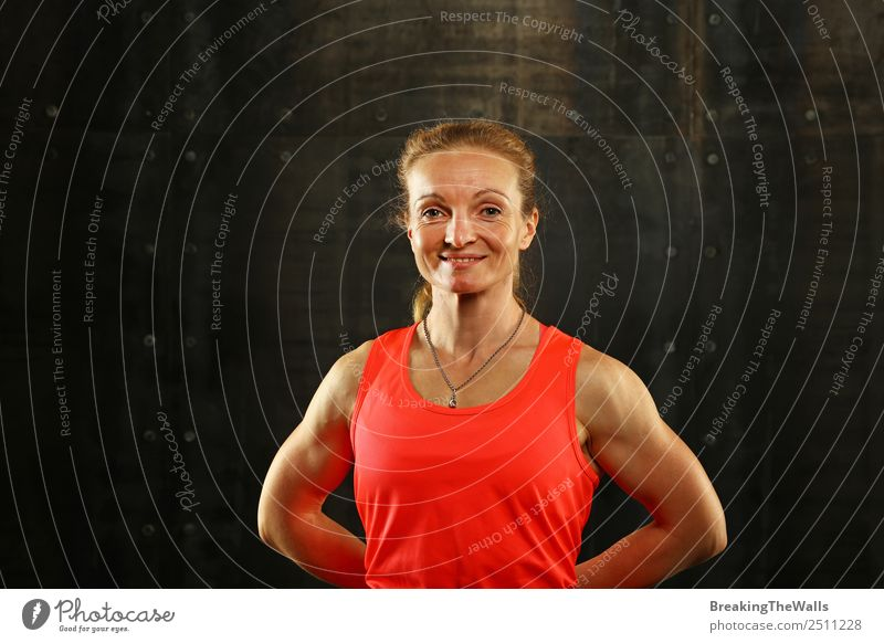 Close up front upper body portrait of one middle age athletic woman in sportswear in gym over dark background, looking at camera and smiling Lifestyle Sports