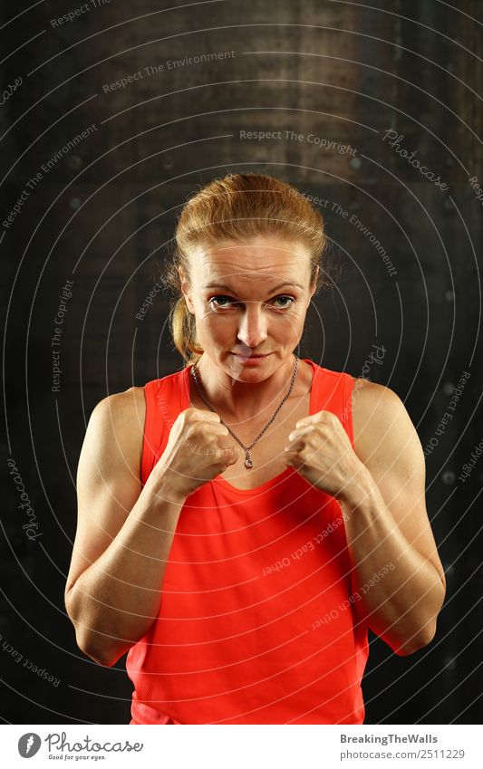 Close up front portrait of one young mid adult athletic woman in sportswear in gym over dark background, standing in boxing stance with hands and fists, looking at camera