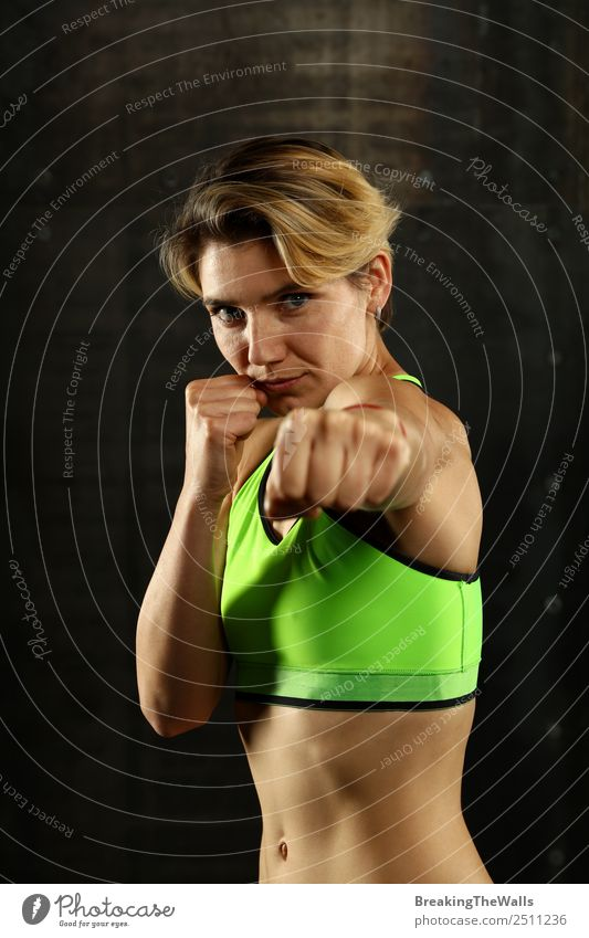 Close up front portrait of one young athletic woman in sportswear in gym over dark background, standing in boxing stance with hands and fists, looking at camera