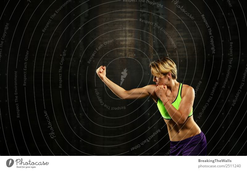 Close up side view profile portrait of one young athletic woman shadow boxing in sportswear in gym over dark background, looking away Sports Fitness
