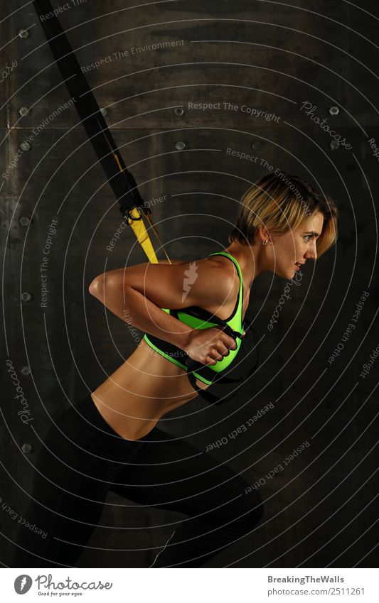 Side profile view portrait of one young athletic woman at crossfit training, exercising with trx suspension fitness straps over dark background, looking away