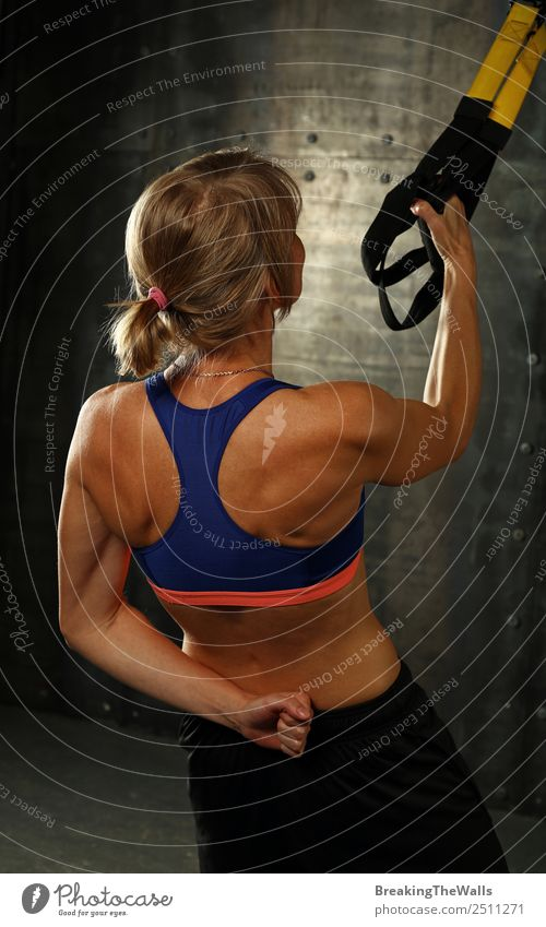 Rear view portrait of one young middle age athletic woman at crossfit training, exercising with trx suspension fitness straps over dark background Lifestyle