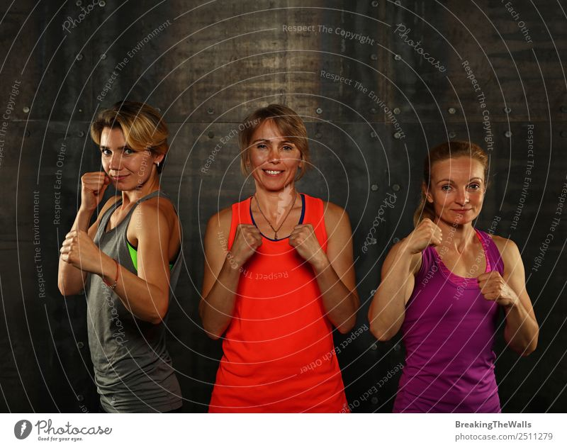 Close up front portrait of three young and middle age athletic women in sportswear in gym over dark background, standing in boxing stance looking at camera