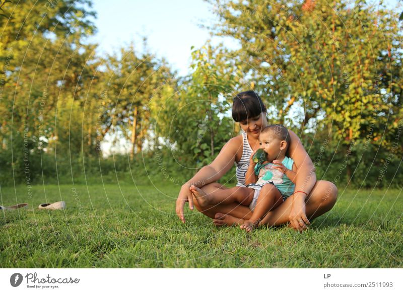 mother holding child eating a cucumber in a beautiful garden Lifestyle Leisure and hobbies Playing Mother's Day Human being Child Baby Young woman