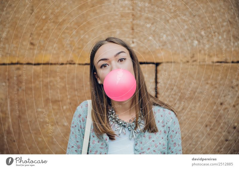 Young girl blowing bubble gum over a stone wall background Lifestyle Joy Happy Beautiful Face Human being Woman Adults Youth (Young adults) Mouth Lips Fashion
