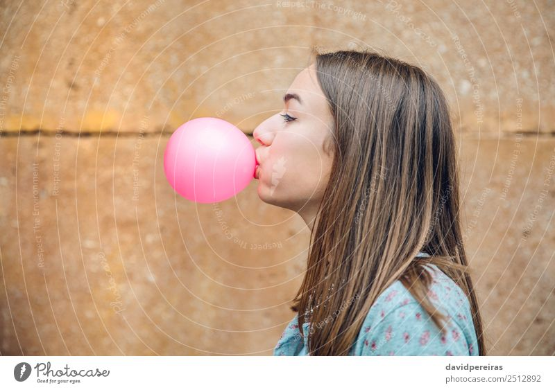 Young teenage girl blowing pink bubble gum over stone wall background Lifestyle Joy Happy Beautiful Face Human being Woman Adults Youth (Young adults) Mouth