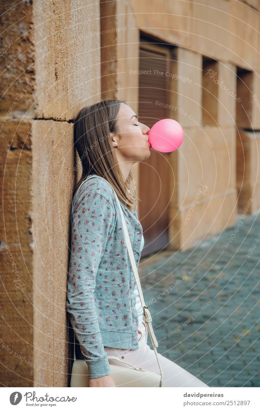 Young teenage girl blowing pink bubble gum Lifestyle Joy Happy Beautiful Face Calm Human being Woman Adults Youth (Young adults) Mouth Lips Fashion Brunette