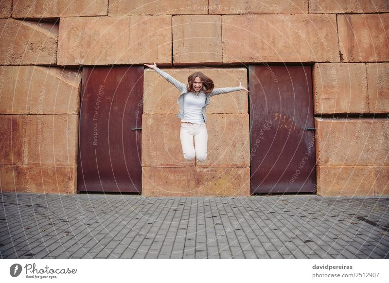 Portrait of happy young woman jumping outdoors Lifestyle Joy Happy Beautiful Leisure and hobbies Freedom Human being Woman Adults Street Fashion Clothing Jeans