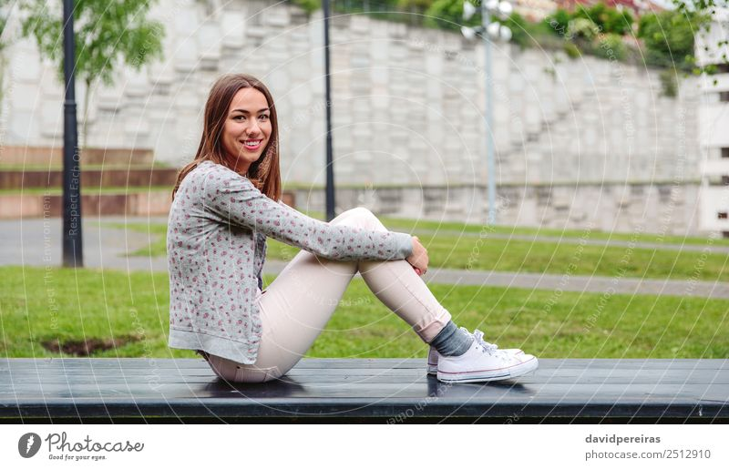Beautiful young woman sitting on park bench Lifestyle Style Happy Leisure and hobbies Human being Woman Adults Nature Autumn Grass Park Fashion Clothing Jeans