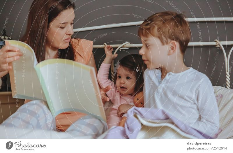 Mother reading book to her sons in the bed Woman Child Beautiful Relaxation House (Residential Structure) Joy Adults Lifestyle Love Family & Relations Happy