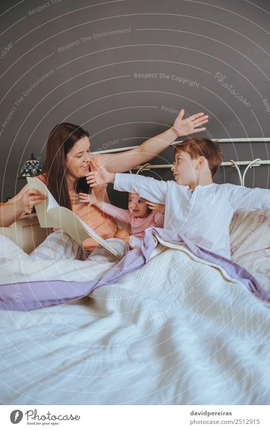 Mother reading book to her sons in the bed Lifestyle Joy Happy Beautiful Relaxation Leisure and hobbies Reading House (Residential Structure) Bedroom Child Baby