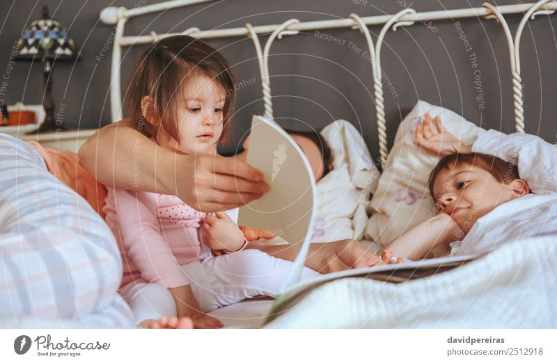 Baby girl reading book with family in the bed Lifestyle Joy Happy Beautiful Relaxation Leisure and hobbies Reading Bedroom Child Boy (child) Woman Adults