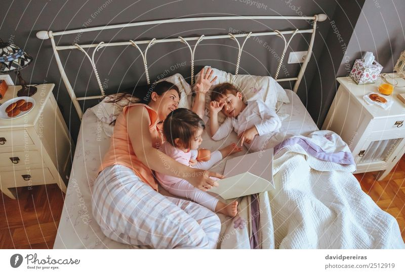 Mother reading book to her sons in the bed Lifestyle Joy Happy Beautiful Relaxation Leisure and hobbies Reading Bedroom Child Baby Boy (child) Woman Adults