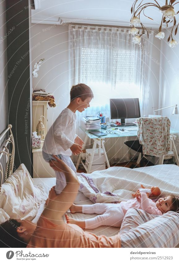 Boy jumping over the bed with his family Lifestyle Joy Happy Beautiful Relaxation Leisure and hobbies Playing Bedroom Child Baby Boy (child) Woman Adults