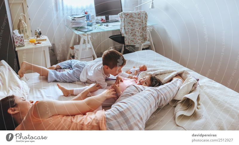 Relaxed mother and sons playing over the bed Woman Child Beautiful Relaxation Joy Adults Lifestyle Love Family & Relations Laughter Happy Boy (child) Playing