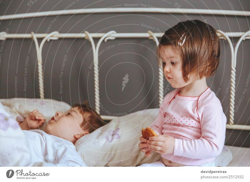 Little girl holding cookie sitting over the bed Eating Breakfast Lifestyle Joy Relaxation Leisure and hobbies Bedroom Child Baby Boy (child) Woman Adults