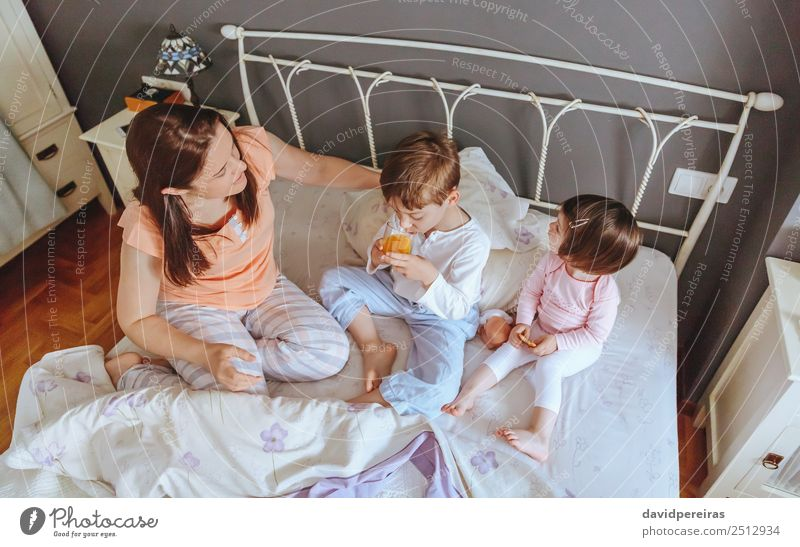 Relaxed children having breakfast over the bed Eating Breakfast Juice Lifestyle Joy Happy Beautiful Relaxation Leisure and hobbies Bedroom Child Baby