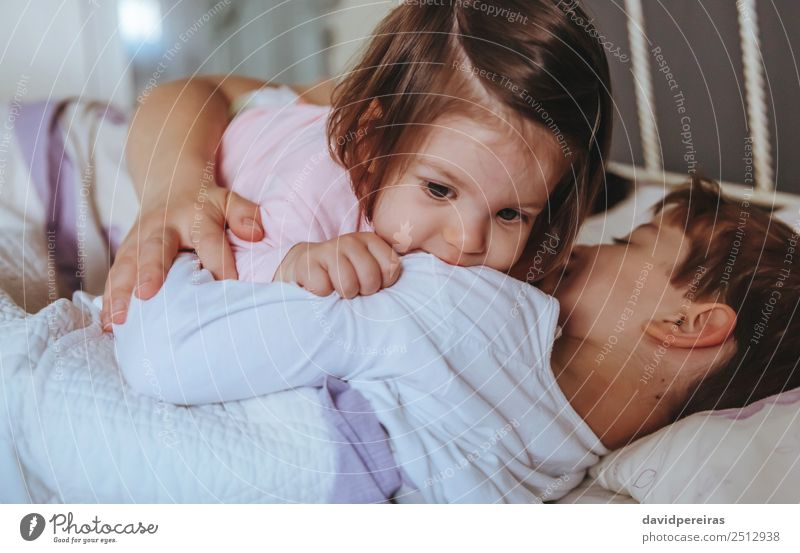 Little girl playing over boy lying in the bed Woman Child Relaxation Joy Adults Lifestyle Love Family & Relations Laughter Happy Boy (child) Small Playing