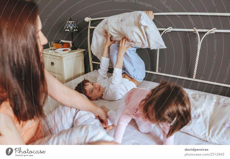 Relaxed mother and sons playing over the bed Lifestyle Joy Happy Beautiful Relaxation Leisure and hobbies Playing Bedroom Child Baby Boy (child) Woman Adults