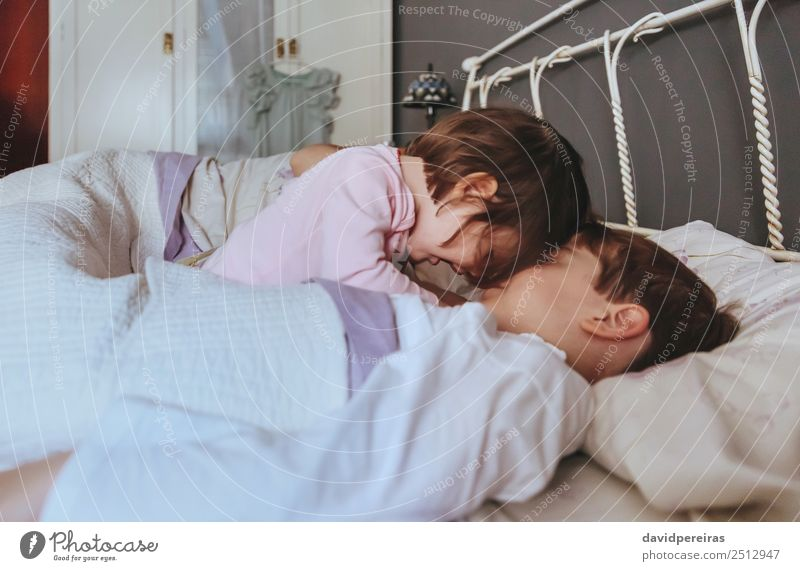 Little girl playing with boy over the bed Lifestyle Joy Happy Beautiful Relaxation Leisure and hobbies Playing Bedroom Child Baby Boy (child) Woman Adults