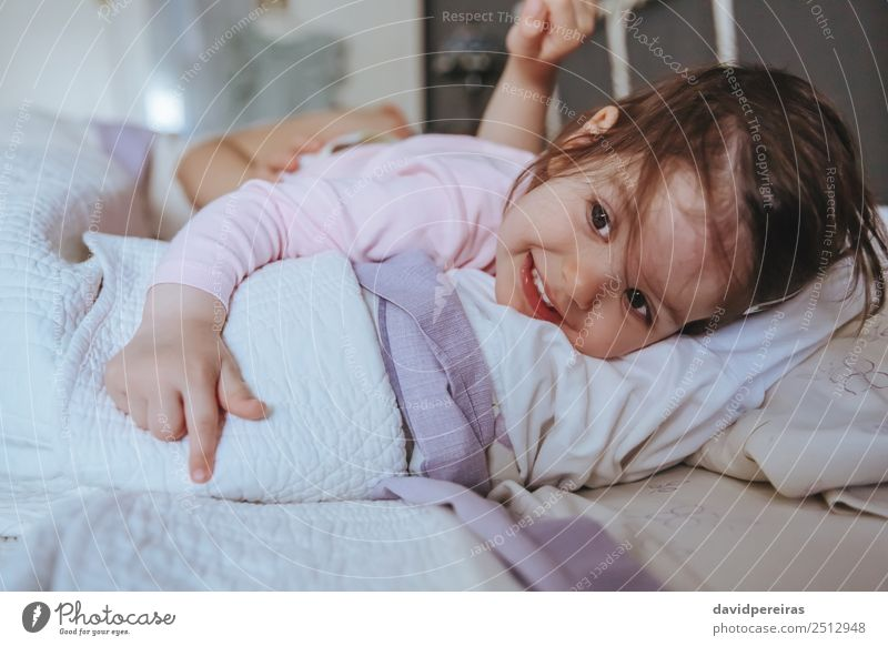 Little girl smiling lying over the bed Lifestyle Joy Happy Relaxation Leisure and hobbies Playing Bedroom Child Human being Baby Woman Adults Parents Mother