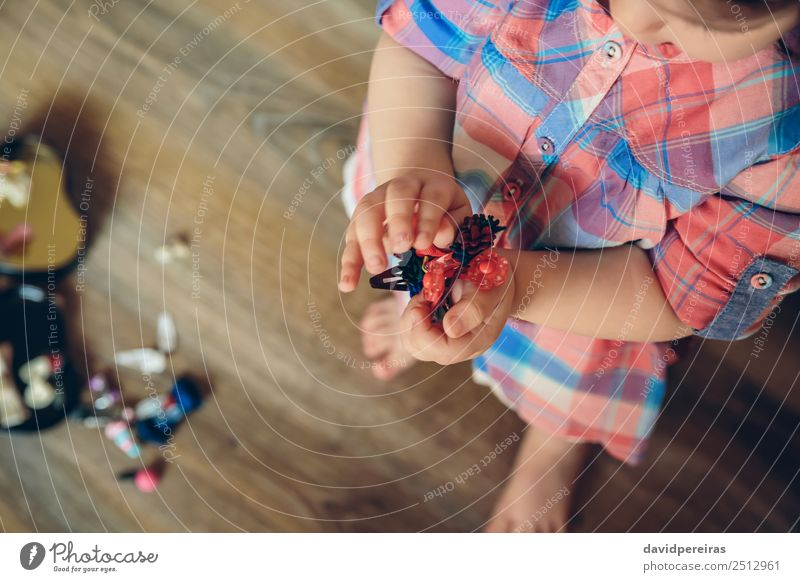 Baby girl playing with hair clips in the hands Woman Child Human being Beautiful Hand House (Residential Structure) Joy Adults Lifestyle Love Wood Happy Small