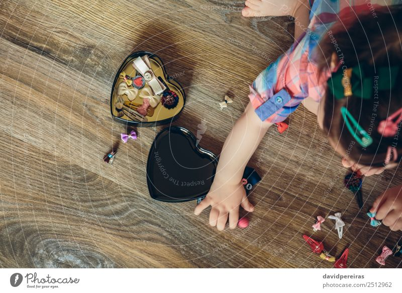 Baby girl playing with hair clips sitting in the floor Lifestyle Joy Happy Beautiful Playing Child Human being Woman Adults Infancy Hand Aircraft Accessory
