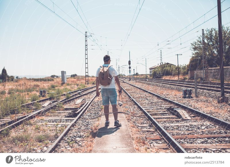 man walking by train Beautiful Vacation & Travel Trip Business Human being Man Adults Grass Transport Street Railroad Line Modern Blue Green Black White
