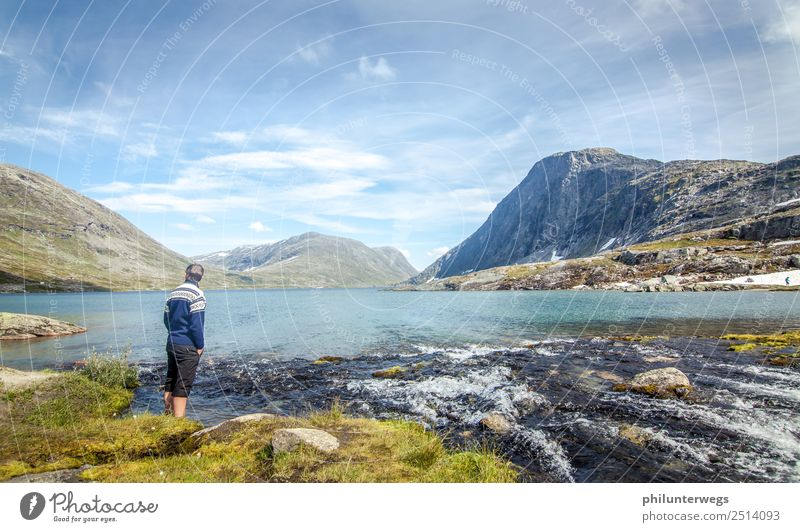 Man stands with feet in the water in the mountain lake Environment Nature Landscape Clouds Summer Beautiful weather Rock Alps Mountain Peak Coast Lakeside Bay
