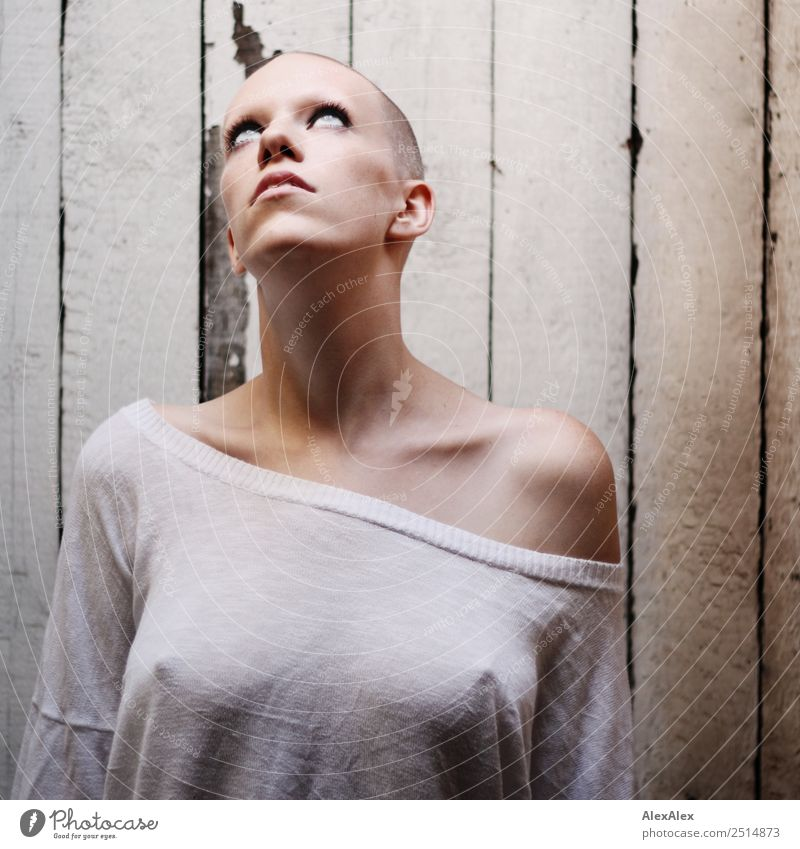 Portrait of a young, very short-haired woman wearing an off-the-shoulder top through which you can see her nipples Style Exotic pretty Calm Young woman