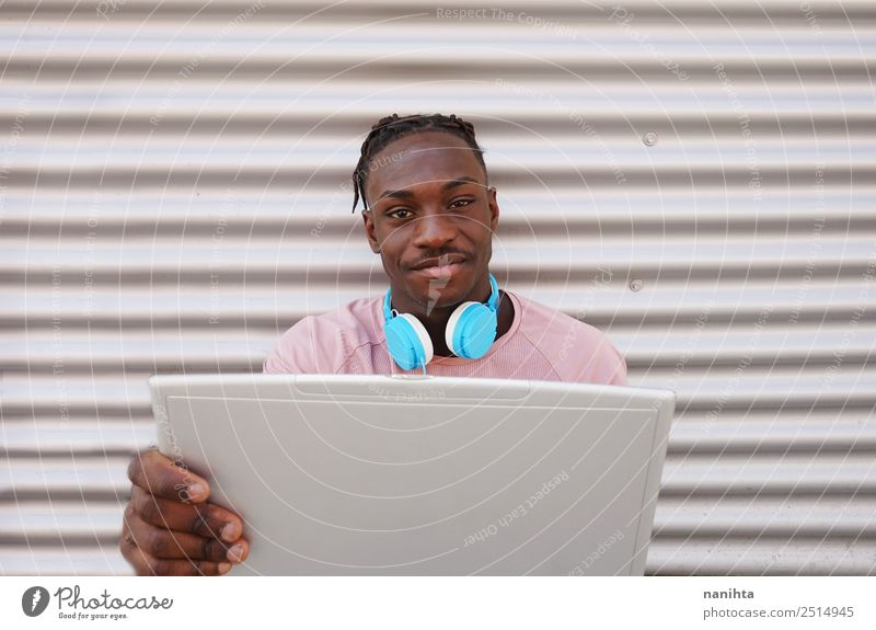 Young black man using his laptop Lifestyle Style Design Student Headset Computer Headphones Notebook Technology Entertainment electronics Internet Human being