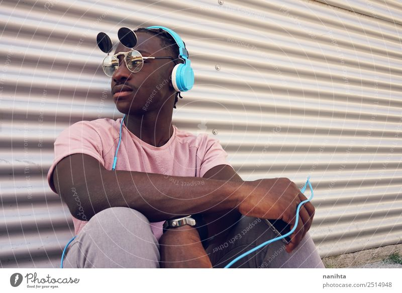 young black man listening music with his phone Lifestyle Style Design Leisure and hobbies Cellphone Headset Headphones Technology Entertainment electronics