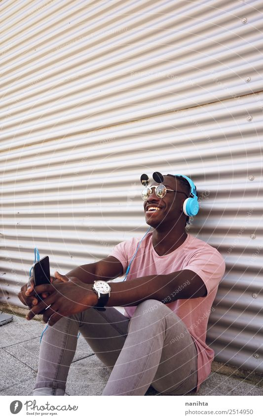 Young happy man listening to music Lifestyle Elegant Style Joy Leisure and hobbies Cellphone Headset Headphones Technology Entertainment electronics Human being