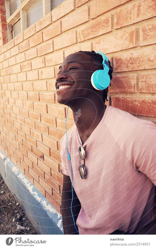 Young happy black man is listening to music Lifestyle Style Joy Wellness Well-being Contentment Headset Headphones Technology Entertainment electronics