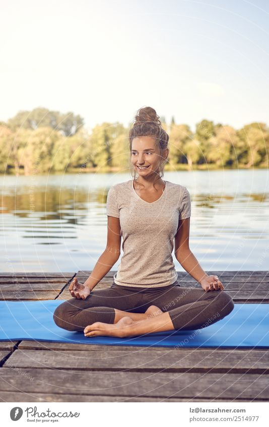 Smiling woman sitting meditating on a wooden deck Lifestyle Happy Body Wellness Meditation Summer Ocean Yoga Woman Adults 1 Human being 18 - 30 years