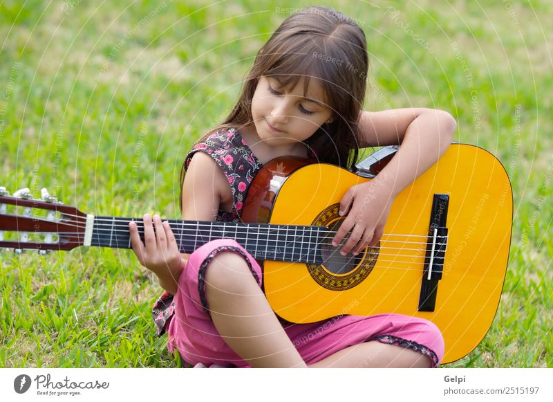 Girl with a guitar Joy Happy Beautiful Playing Music Child Human being Infancy Hand Fingers Guitar Musical notes Grass Sit Happiness Small Cute Green Pink