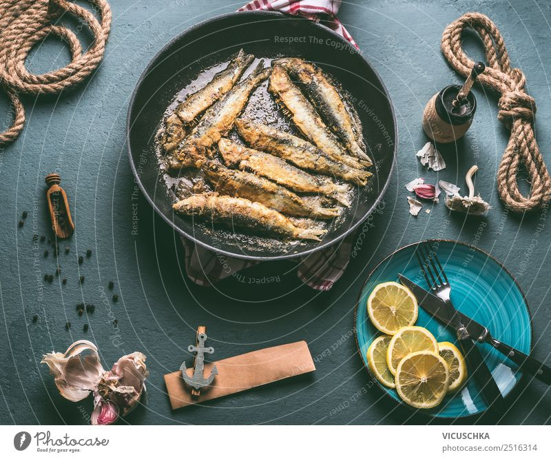 Fried sardines in a pan on the kitchen table with ingredients Food Fish Nutrition Dinner Organic produce Vegetarian diet Crockery Plate Pan Cutlery Style Design