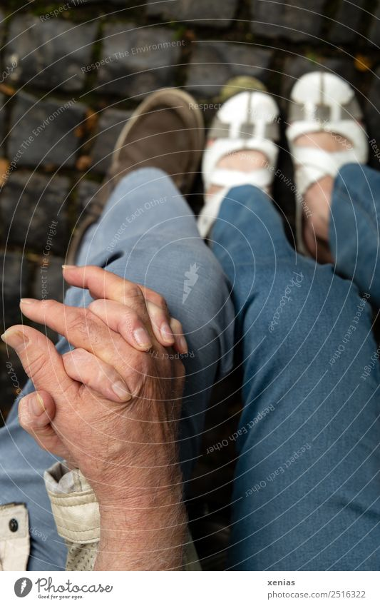 Senior couple holding hands Senior citizen by hand Woman Adults Man Couple Partner Fingers Legs 2 Pants Jeans Footwear Hold hands Sit Blue Gray White luck Trust
