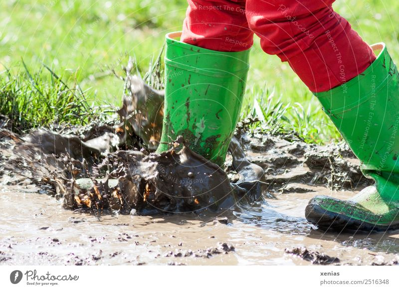 Muddling in the puddle with green rubber boots Joy Child Infancy Legs 1 Human being 3 - 8 years 8 - 13 years Jeans Boots Rubber boots Jump Dirty Brown Green Red