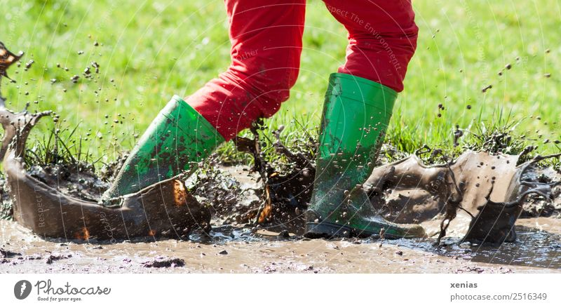 Walking through mud with green rubber boots Girl Young woman Youth (Young adults) Legs 1 Human being Grass Pants Jeans Boots Rubber boots Going Playing Jump