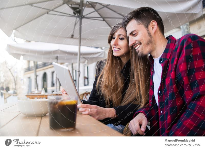 young couple sitting at a terrace Lifestyle Happy Leisure and hobbies Vacation & Travel Table Restaurant Computer Technology Internet Woman Adults Man
