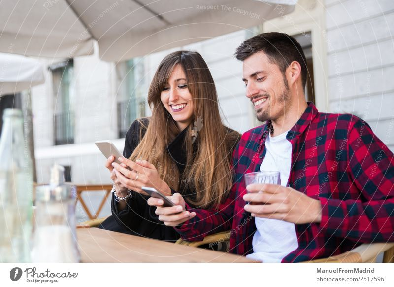 young couple sitting at a terrace Lifestyle Happy Leisure and hobbies Vacation & Travel Table Restaurant Telephone PDA Technology Internet Woman Adults Man