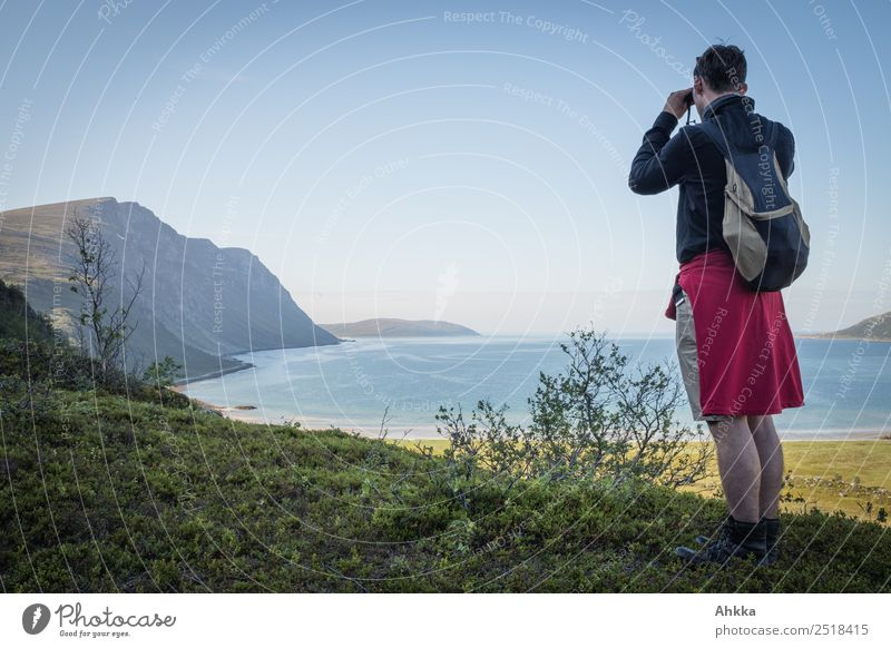 Young man looks through a ferrule at a fjord Relaxation Vacation & Travel Trip Adventure Far-off places Freedom Hiking Youth (Young adults) Landscape Fjord