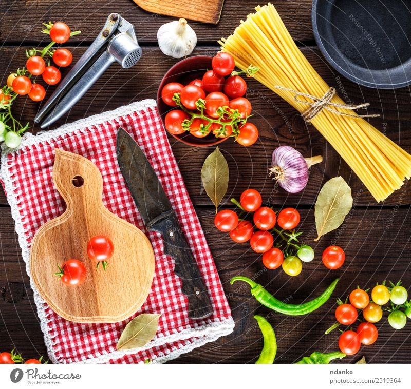 red cherry tomatoes and spaghetti Vegetable Dough Baked goods Herbs and spices Lunch Dinner Pan Knives Wood Line Eating Fresh Large Long Above Brown Yellow Red