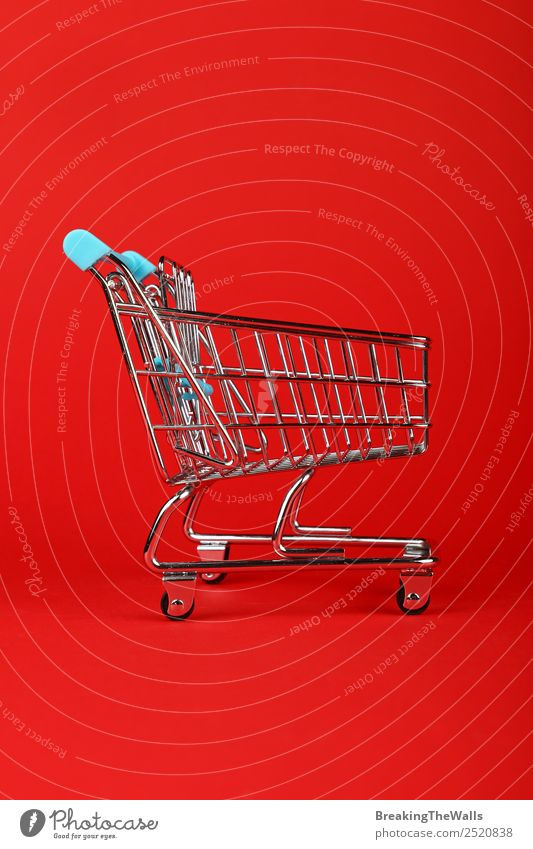 Empty toy supermarket shopping cart over red background Toys Metal Small Red Shopping Shopping Trolley Shopping basket Cart Retail sector Consumption Profile