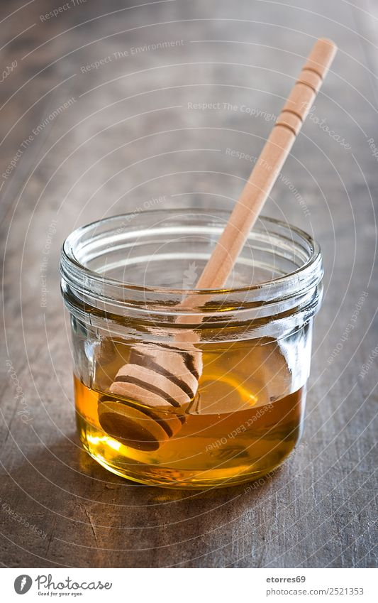 Honey dipper with honey in a jar on wood Food Candy Nutrition Diet Bottle Glass Spoon Healthy Healthy Eating Wood Fluid Sweet Liquid Food photograph Vitamin