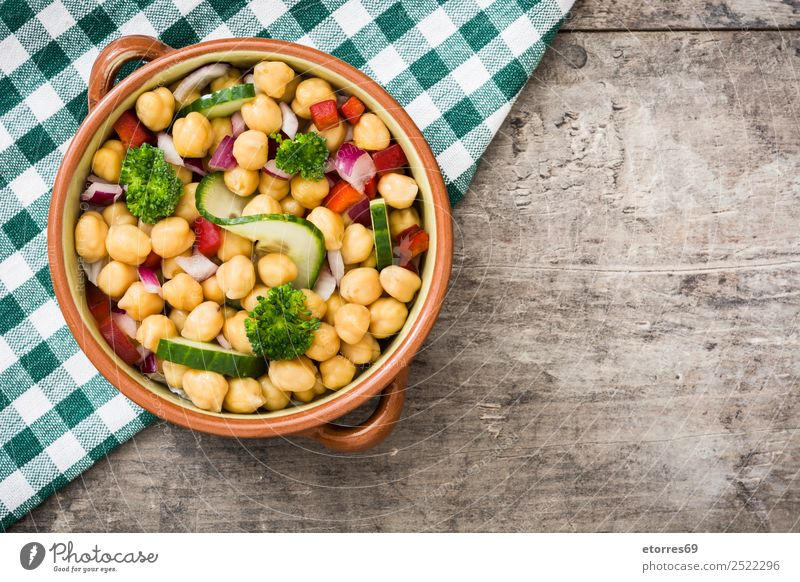 Chickpea salad in bowl on wooden background champagne
