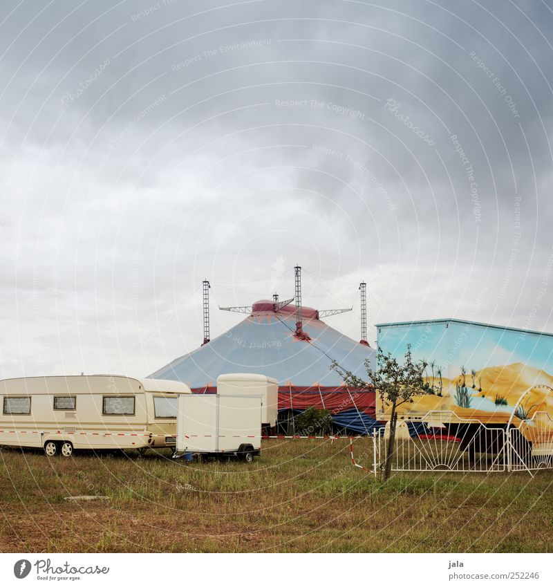 circus Sky Clouds Plant Tree Grass Manmade structures Truck Caravan Trailer Gloomy Tent Circus Circus tent Circus trailer Colour photo Exterior shot Deserted